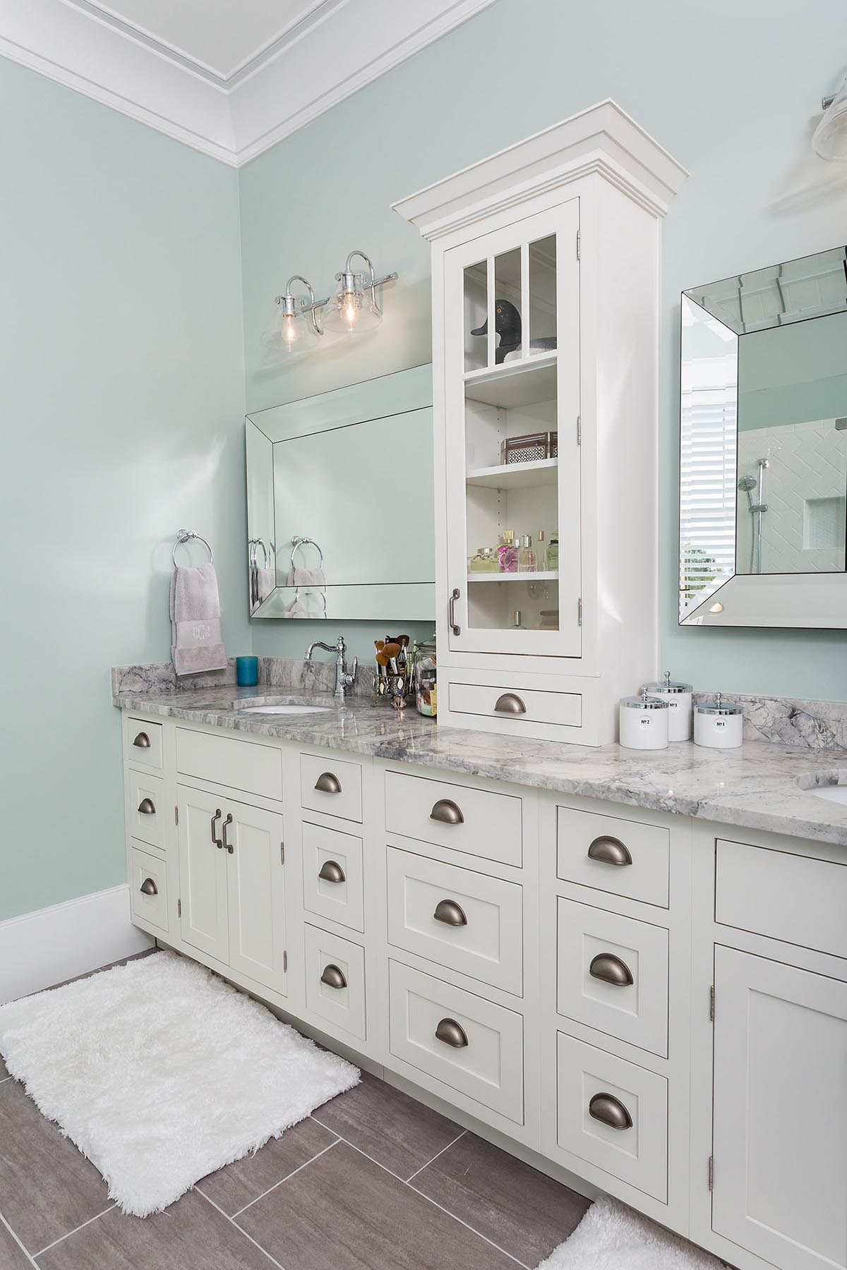 Owners ensuite (master bath) in new home includes custom vanity featuring inset cabinets, glass display case stacked on counter and gray marble vanity to with undermount sinks and vintage-look light fixtures.
