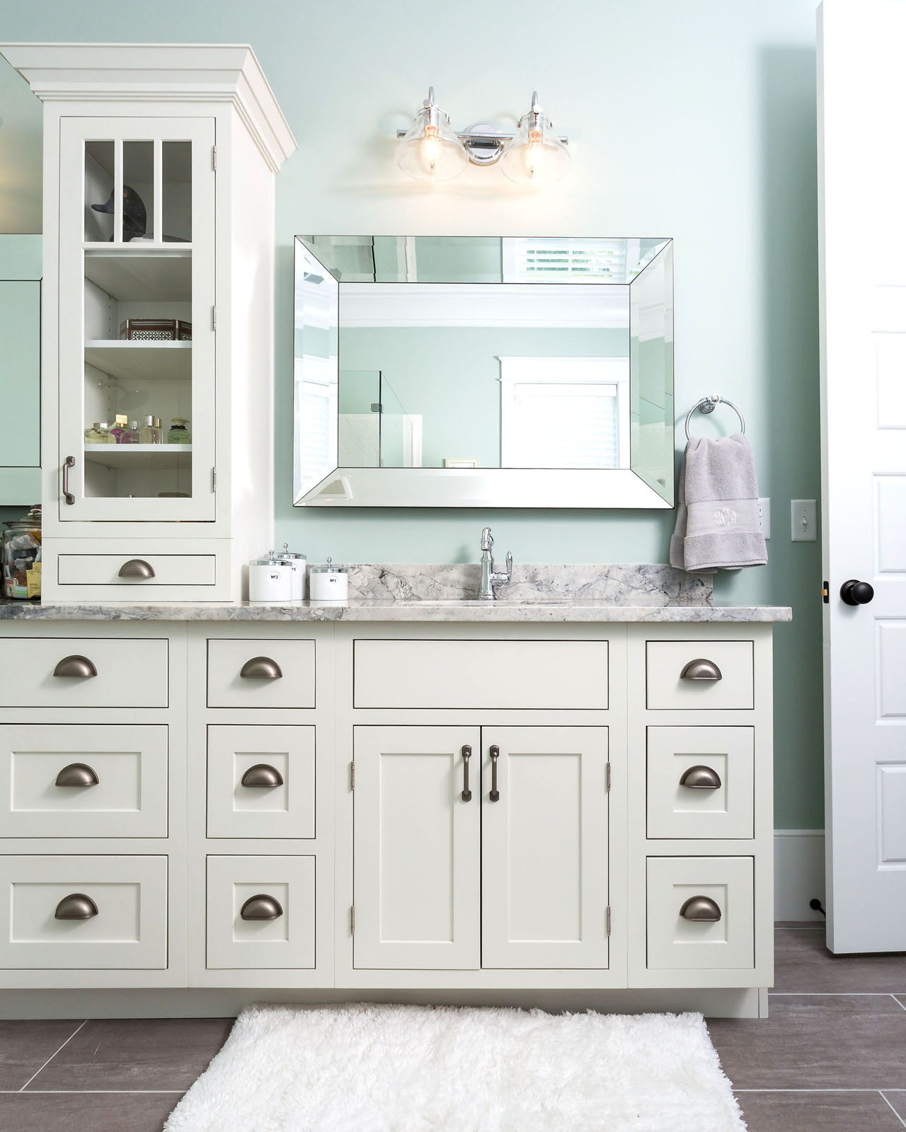 CliqStudios bath cabinets shown in Austin White door style and finish