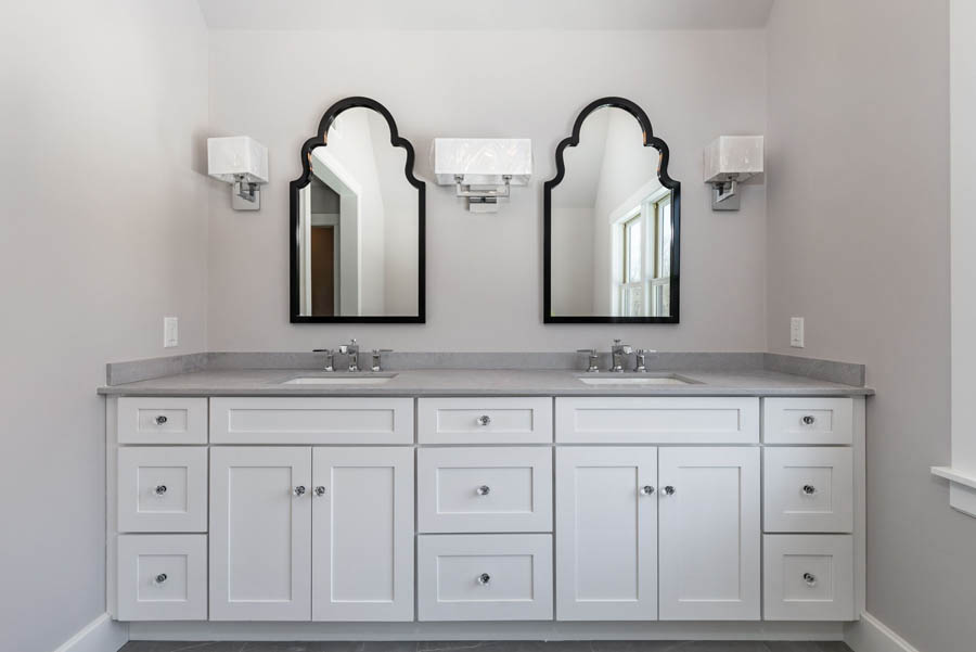 double vanity with white Shaker cabinets, gray countertop with two black beveled mirrors above