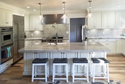Large kitchen with white cabinets, island with seating, wood floors and professional stainless steel appliances
