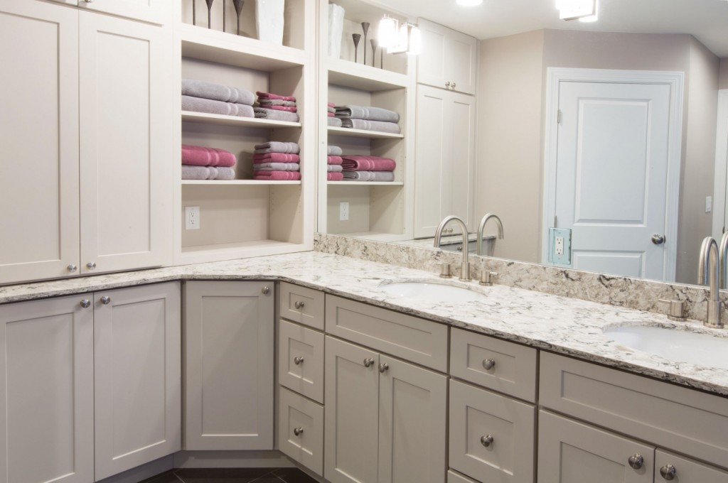 bath has generous cabinetry, including double vanity, open shelves and ceiling-high stacked cabinets in white shaker style with brushed nickel trim