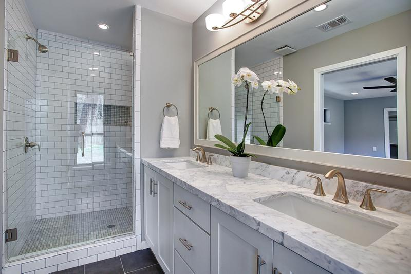 double vanity in white bath is built of semi-custom shaker cabinets topped with white marble